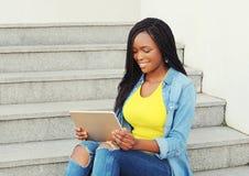 Mujer africana sonriente hermosa que usa el ordenador de la PC de la tableta Fotos de archivo