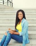 Mujer africana sonriente hermosa que usa el ordenador de la PC de la tableta Imágenes de archivo libres de regalías