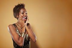 Mujer africana sonriente que parece sorprendida Fotos de archivo