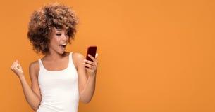 Mujer afro alegre que usa el teléfono elegante Imágenes de archivo libres de regalías