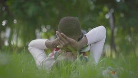 Mujer afroamericana adorable que miente en la hierba en el parque, su peque?o hijo que se sienta encima de ella que toca su cara almacen de video