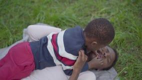 Mujer afroamericana adorable que miente en la hierba en el parque, su peque?o hijo que se sienta encima de ella que toca su cara almacen de metraje de vídeo