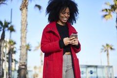 Mujer afroamericana alegre encantadora que se coloca en paisaje urbano el día soleado usando el artilugio y la radio 5G Fotografía de archivo