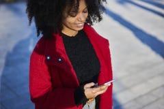 Mujer afroamericana alegre encantadora que usa la conexión inalámbrica a Internet Imagenes de archivo