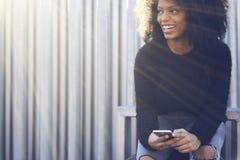 Mujer afroamericana alegre encantadora que usa la conexión inalámbrica libre a Internet y al smartphone moderno Fotos de archivo libres de regalías