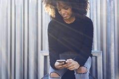 Mujer afroamericana alegre encantadora que usa la conexión inalámbrica y el smartphone libres Fotos de archivo