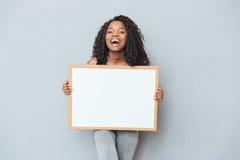 Mujer afroamericana alegre que muestra al tablero en blanco imagen de archivo