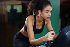Mujer afroamericana apta que ejercita en la bici de giro en la clase cardiia en el gimnasio Imagen de archivo libre de regalías