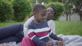 Mujer afroamericana atractiva del retrato que miente en la manta con su peque?o hijo en el parque La madre joven almacen de metraje de vídeo