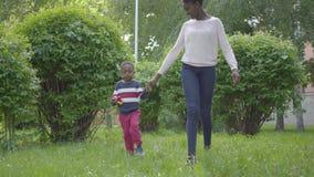 Mujer afroamericana atractiva que camina en el parque con su peque?o hijo, llevando a cabo las manos Tiempo lindo del gasto del n metrajes