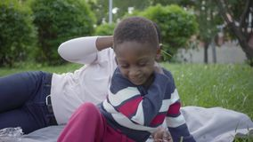 Mujer afroamericana atractiva que miente en la manta con su peque?o hijo en el parque La madre joven cosquillea al muchacho almacen de metraje de vídeo
