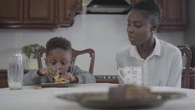 Mujer afroamericana atractiva que se sienta con su peque?o hijo por la tabla que juega las galletas en la placa lazo almacen de metraje de vídeo