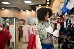 Mujer afroamericana atractiva sonriente de los jóvenes que elige talla de sujetador correcta en tienda de la ropa interior Muchac fotografía de archivo libre de regalías