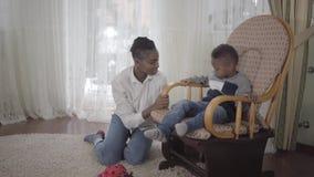Mujer afroamericana bonita alegre que juega con su pequeño hijo lindo y divertido que se sienta en una mecedora en sala de estar metrajes