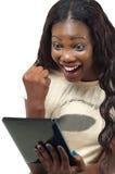 Mujer afroamericana bonita feliz usando una PC de la tableta Imagenes de archivo