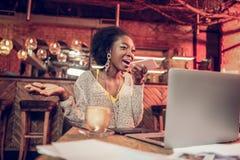 Mujer afroamericana brillante que tiene una conversación telefónica del negocio en restaurante fotografía de archivo