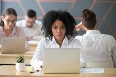 Mujer afroamericana chocada que mira el ordenador portátil subrayado con o Fotos de archivo libres de regalías