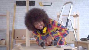 Mujer afroamericana con el peinado del Afro que mira la cámara y que sonríe haciendo las reparaciones, artesanía en madera metrajes