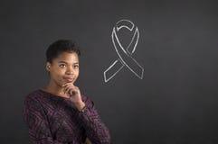 Mujer afroamericana con la mano en la barbilla que piensa en conciencia de la enfermedad en fondo de la pizarra Foto de archivo