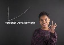 Mujer afroamericana con la señal de mano perfecta que muestra el desarrollo personal en fondo de la pizarra Fotografía de archivo