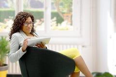 Mujer afroamericana con las lentes y la tableta imagen de archivo libre de regalías