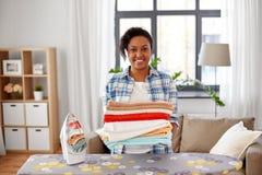 Mujer afroamericana con lino planchado en casa imagenes de archivo