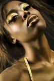 Mujer afroamericana con maquillaje de oro Imágenes de archivo libres de regalías