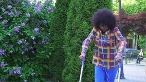 Mujer afroamericana con un peinado afro con una pierna quebrada en las muletas MES lento almacen de metraje de vídeo