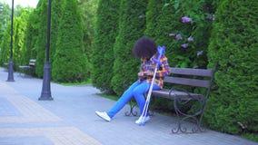 Mujer afroamericana con un peinado afro con una pierna quebrada con las muletas que se sientan en un banco almacen de metraje de vídeo