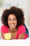 Mujer afroamericana con una hucha Fotografía de archivo libre de regalías