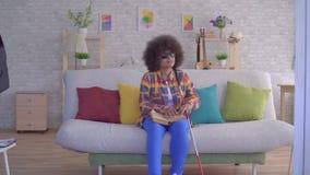 Mujer afroamericana con una persona con deficiencias visuales afro del peinado que lee un libro con sus fingeres metrajes