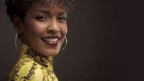 Mujer afroamericana de la raza mixta en vestido amarillo brillante con la impresión del pitón estilo de 90 ` s metrajes