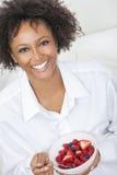 Mujer afroamericana de la raza mixta que come la fruta Foto de archivo libre de regalías