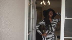 Mujer afroamericana de moda elegante en sombrero negro y el vestido rayado que presentan en sus apartamentos de lujo almacen de metraje de vídeo