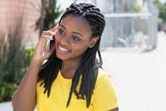 Mujer afroamericana de risa en una camisa amarilla en el teléfono móvil Foto de archivo