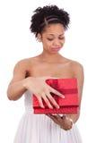 Mujer afroamericana decepcionada que abre una caja de regalo Imagenes de archivo
