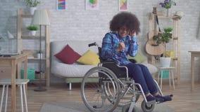 Mujer afroamericana discapacitada alegre con un peinado afro en una silla de ruedas en auriculares que escucha la m?sica almacen de video