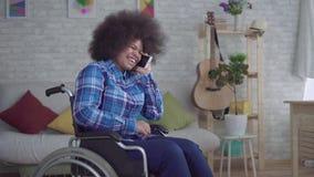 Mujer afroamericana discapacitada con un peinado afro en una diversión de la silla de ruedas que habla en el teléfono almacen de video