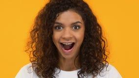 Mujer afroamericana emocionada impresionada por buenas noticias, guau gesto, positividad almacen de metraje de vídeo
