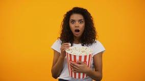 Mujer afroamericana emocionada que come las palomitas y que mira película interesante almacen de metraje de vídeo