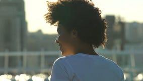 Mujer afroamericana emocionada que disfruta del aire libre del sol de la mañana, alegría, visión trasera metrajes