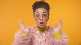 Mujer afroamericana en capa rosada divertida sorprendida por las noticias interesantes, chisme almacen de video