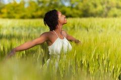 Mujer afroamericana en un campo de trigo Imagen de archivo