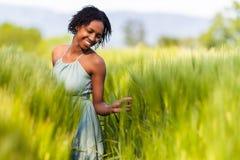 Mujer afroamericana en un campo de trigo Fotos de archivo
