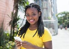 Mujer afroamericana en un mensaje que mecanografía de la camisa amarilla con el teléfono móvil Imagen de archivo