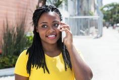 Mujer afroamericana en una camisa amarilla que escucha en el teléfono móvil Fotografía de archivo libre de regalías