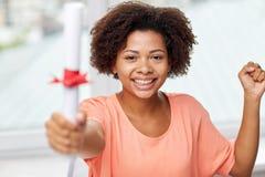 Mujer afroamericana feliz con el diploma en casa Foto de archivo libre de regalías