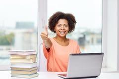 Mujer afroamericana feliz con el ordenador portátil en casa Fotografía de archivo