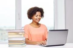 Mujer afroamericana feliz con el ordenador portátil en casa Imagen de archivo libre de regalías