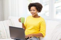 Mujer afroamericana feliz con el ordenador portátil en casa Imagenes de archivo